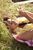 Teenage girl lying on grass with phone Stock Images