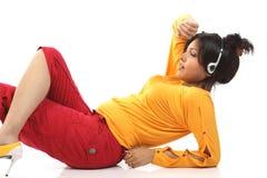 Teenage girl lying with headphones. Beautiful teenage girl lying on the floor relaxing listening to music Royalty Free Stock Photography