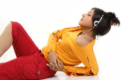 Teenage girl lying with headphones. Beautiful teenage girl lying on the floor relaxing listening to music Royalty Free Stock Image