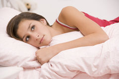 Teenage Girl Lying On Her Bed Looking Sick Stock Photo