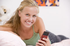 Teenage Girl Lying On Her Bed Using Mobile Phone Stock Photos