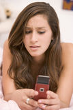 Teenage Girl Lying On Her Bed Using Mobile Phone Stock Photography