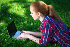 Teenage girl lying with laptop on grass in park Stock Photos