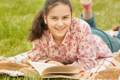 Teenage girl lying on the plaid with a book royalty free stock image