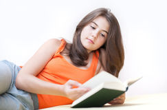 Teenage girl lying and reading a book Stock Photography