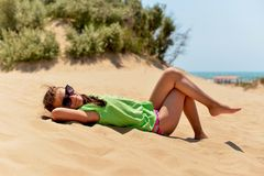 Teenage girl lying on the sandy beach stock photos