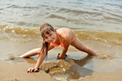 Teenage girl lying on the sandy beach stock photography