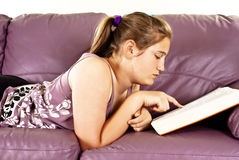 Teenage girl lying on a sofa and reading a book Royalty Free Stock Photography