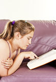 Teenage girl lying on a sofa and reading a book Royalty Free Stock Photo