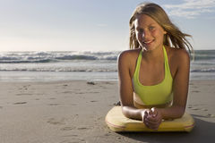 Teenage girl (17-19) lying on top of bodyboard on sandy beach, smiling, front view, portrait Stock Photos