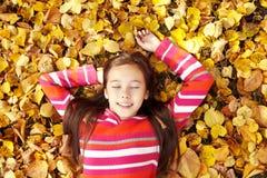 Teenage girl lying on yellow leaves royalty free stock photo