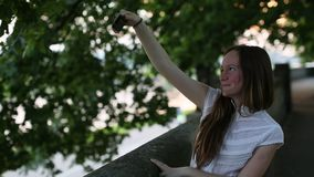 Teenage girl makes a selfie on smartphone, taking pictures of himself. stock footage