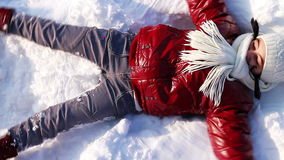 Teenage girl makes a snow angel Stock Images