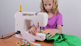 A teenage girl makes a string of thread stock video