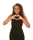 Teenage girl making heart. Teenage girl wearing brown dress with long brunette hair making a heart shape with her hands Stock Photo