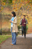 Teenage Girl Making Mobile Phone Call. With Boyfriend Running Towards Her In Background Stock Photo