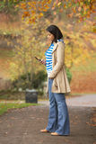 Teenage Girl Making Mobile Phone Call. In Autumn Landscape Stock Images