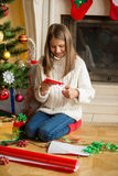 Teenage girl making paper snowflakes at living room at decorated. Beautiful teenage girl making paper snowflakes at living room at decorated Christmas tree Royalty Free Stock Photo