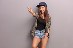 Teenage girl making peace hand gesture Royalty Free Stock Image