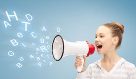 Teenage girl with megaphone. Communication concept - girl with megaphone over blue background Stock Photos