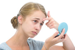 Teenage girl with mirror. Teenage girl checking her face for pimple in the mirror Royalty Free Stock Images
