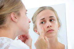 Teenage girl with the mirror. Teenage girl checking her face for pimple in the mirror Stock Photography