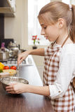 Teenage girl mixing eggs in bowl with whisk Royalty Free Stock Images