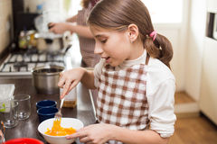 Teenage girl mixing eggs in bowl with whisk Royalty Free Stock Image