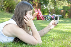 Teenage girl with mobile cell phone relaxing Stock Photography