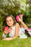 Teenage girl with mobile phone lying grass Royalty Free Stock Image