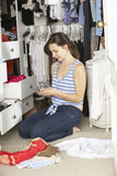Teenage Girl On Mobile Phone Surrounded By Clothes In Wardrobe Stock Photos