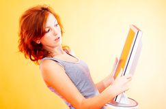 Teenage Girl with Monitor - 2. Young redheaded teenager holds a thin screen television or computer monitor Royalty Free Stock Photos