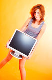 Teenage Girl with Monitor - 4. Young redheaded teenager holding a computer monitor or television screen.  Insert your text on the screen Royalty Free Stock Images