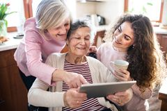 A teenage girl with mother and grandmother at home. A teenage girl with her mother and grandmother in wheelchair at home, using tablet. Family and generations royalty free stock photography