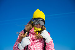 Teenage girl in the mountains. Portrait of young woman with yellow hat and pink sports jacket against the blue sky royalty free stock images