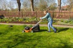 Teenage girl mowing grass Royalty Free Stock Image