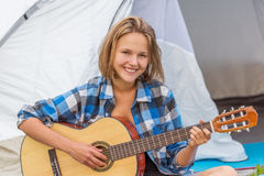 Teenage  girl near the tent playing a guitar Stock Photos