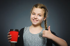 Teenage girl offers red cup of coffee isolated on gray background stock image