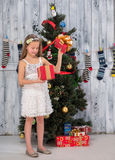 Teenage girl opening Christmas present in front of New Year tree Royalty Free Stock Image