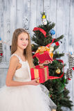 Teenage girl opening Christmas present in front of New Year tree Royalty Free Stock Images