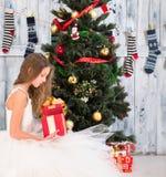 Teenage girl opening Christmas present near New Year tree Stock Photos