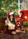 Teenage girl opening her christmas present. Near the christmas tree with decorations. Studio shoot Stock Photo