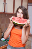 Teenage girl in orange t-shirt biting a slice of watermelon Royalty Free Stock Photography