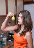 Teenage girl in orange t-shirt holding a green pear Stock Photo