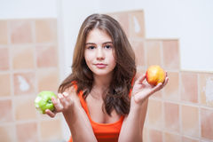 Teenage girl in orange t-shirt looking at camera having a green apple and a peach in her hands Royalty Free Stock Photography