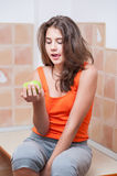Teenage girl in orange t-shirt looking at a green apple Royalty Free Stock Image
