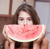 Teenage girl in orange t-shirt looking over a slice of watermelon Royalty Free Stock Photo