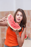 Teenage girl in orange t-shirt showing a slice of watermelon Stock Image