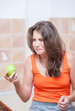 Teenage girl in orange t-shirt trying to eat a green apple Stock Images