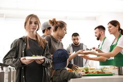 Teenage girl with other poor people receiving food from volunteers. Indoors royalty free stock photo